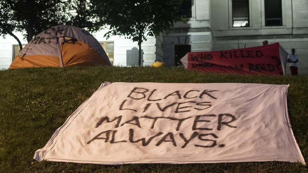 Signs and tents are decorated with Black Lives Matter slogans June 9 in the grass around the Monroe County Courthouse. Some people packed up their tents while others left them standing.