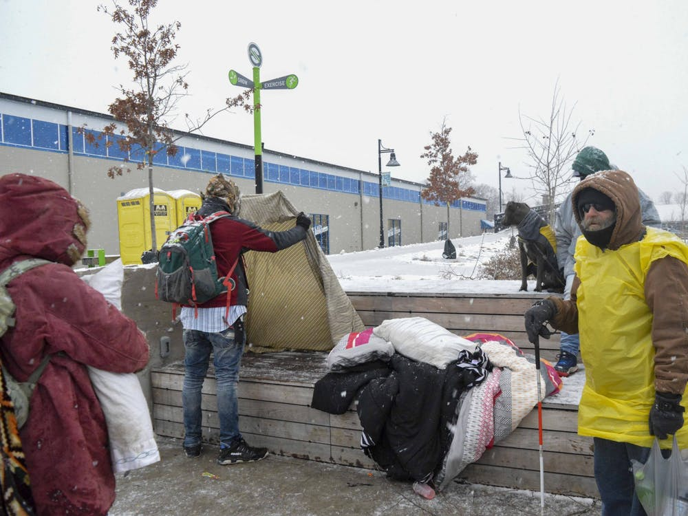 Members of Bloomington's homeless community wait outside A Friend's Place Saturday. The shelter is located at Switchyard Park and opens every evening at 5:15 p.m.