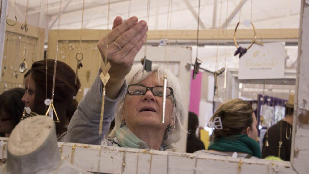 Bloomington resident Dawn Cartwright admires a necklace crafted by Anne Harrill on Nov. 8, 2013, at the Bloomington Handmade Market Saturday at the Convention Center. The market's 2019 holiday show will take place from 10 a.m. to 4 p.m. Nov. 9 at the Monroe Convention Center.
