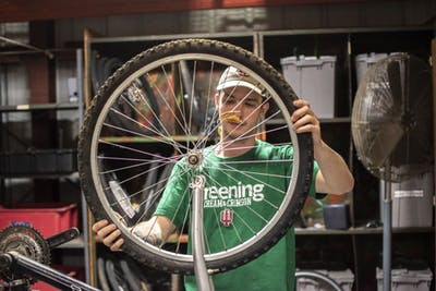 Intern Landon New tests the size of a wheel during the launch of the M1 IU Surplus Bike Shop on April 24 in the IU Surplus Store. New is a geography major at IU.