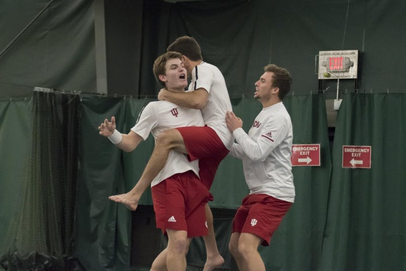 Freshman Andrew Redding is embraced by his teammates after his tough 6-2, 3-6, 7-6 (7-3) singles win over Wisconsin on Sunday at the Indiana University Tennis Center.