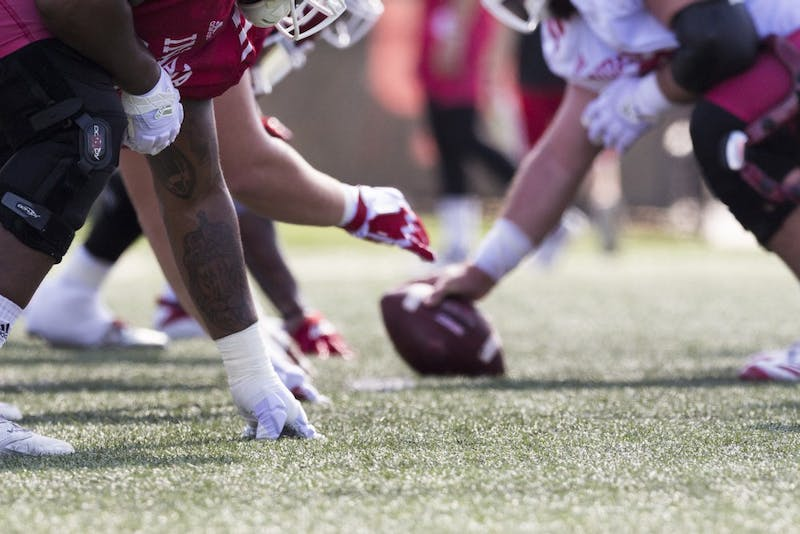 IU football players line up on the scrimmage line Aug. 6, 2018, during practice at the football practice fields.