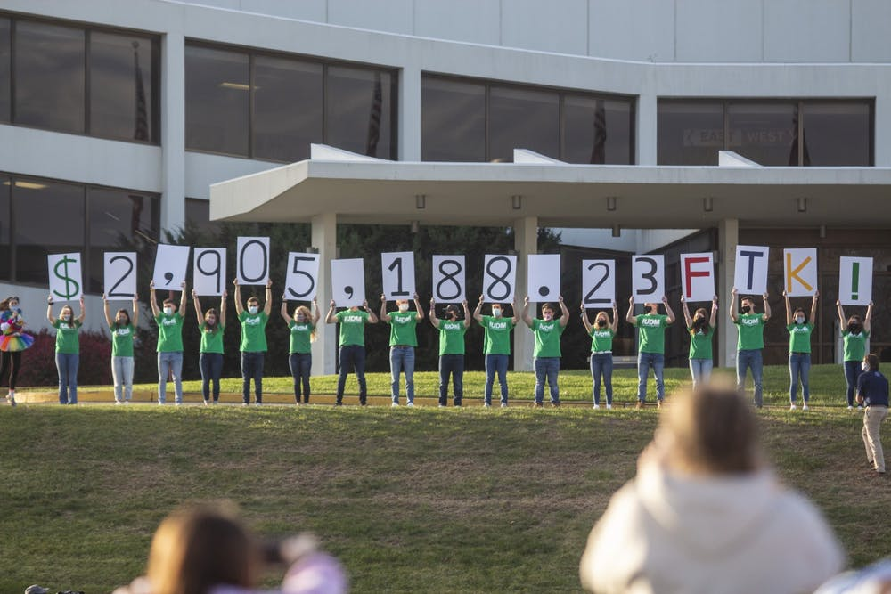 <p>IU Dance Marathon members hold up signs displaying the final total of $2,905,188.23 on Nov. 8 in front of Simon Skjodt Assembly Hall. The dance marathon, which raises money every year for Riley Hospital for Children, took place in a hybrid format this year, with virtual components and in-person components at Dunn Meadow and outside Assembly Hall. </p>