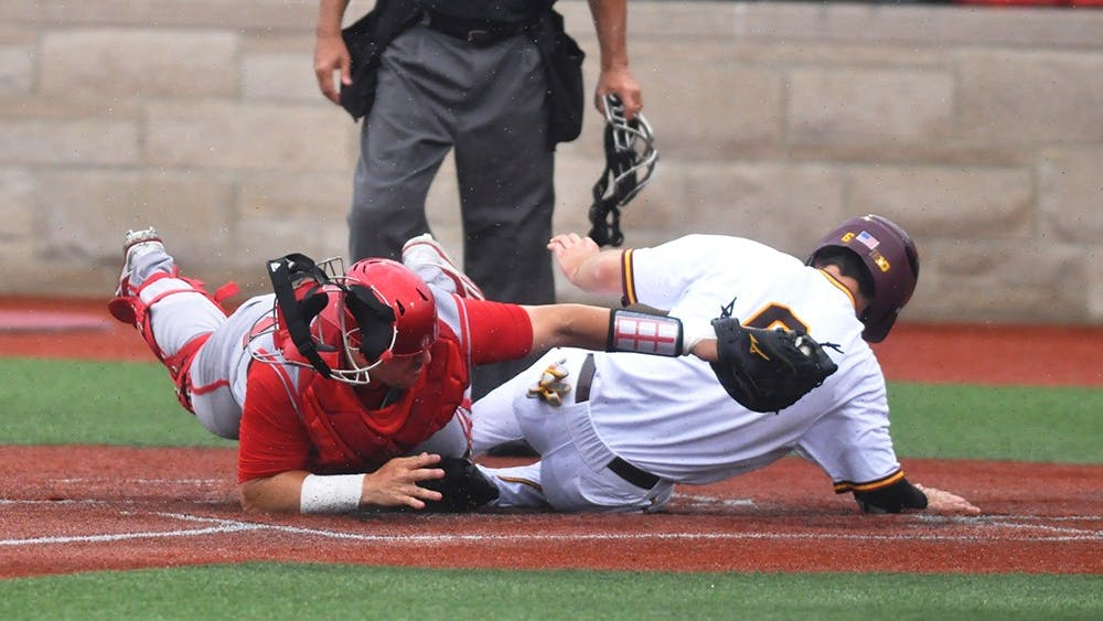 Sophomore catcher Ryan Fineman tries to tag out Minnesota's Terrin Vavra at home plate on May 24, 2017. Vavra scored one of Minnesota's 5 runs in their 5-4 win over the Hoosiers.