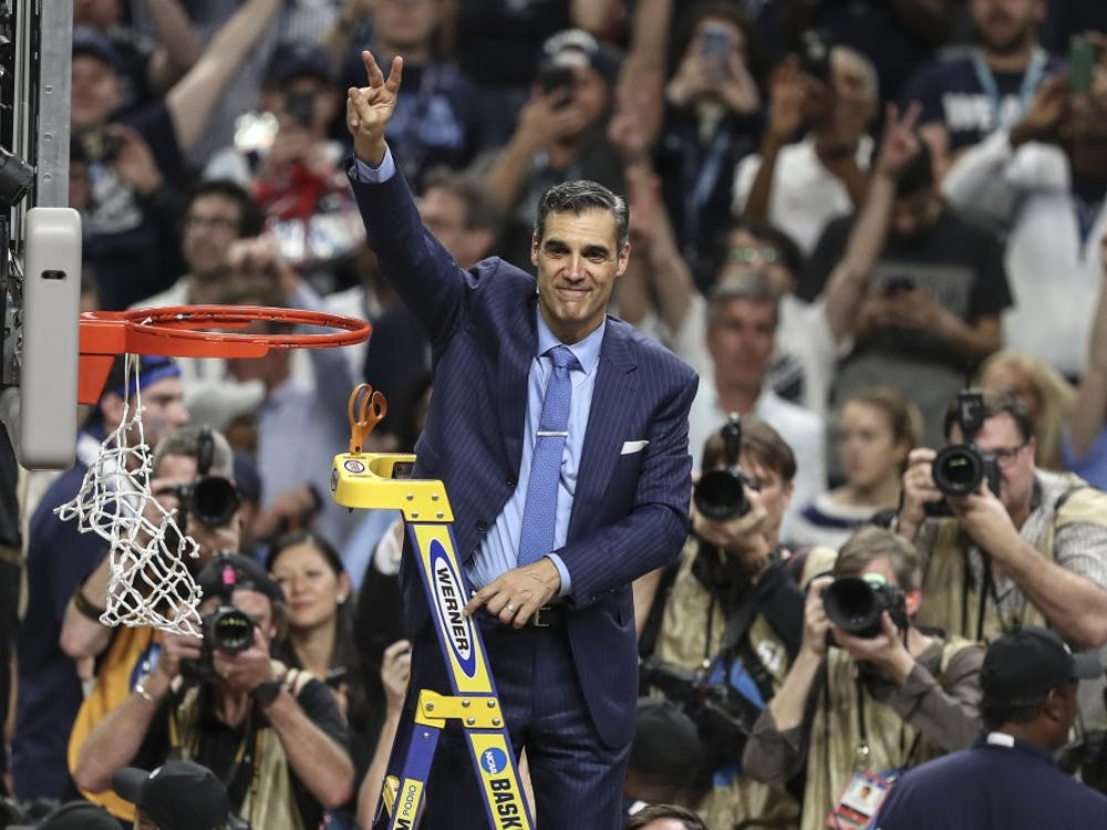 """Villanova head coach Jay Wright waves the Villanova """"V"""" to the fans while cutting the net after beating Michigan to win the NCAA National Championship on Monday, April 2, 2018, at the Alamodome in San Antonio, Texas. The Villanova team is the National Champion, beating Michigan 79-62."""