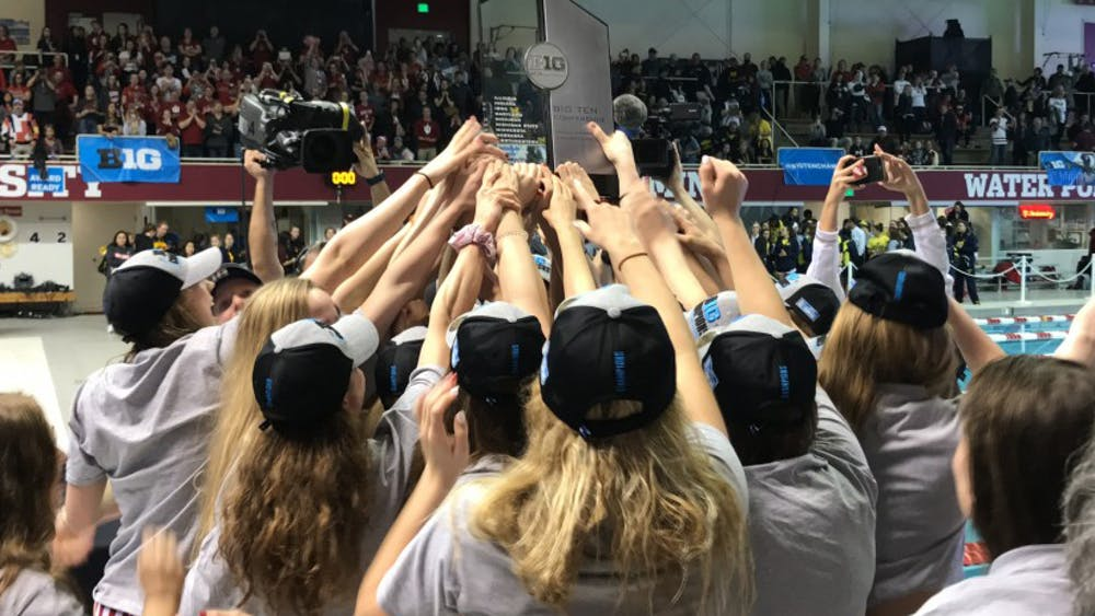 The IU women's swim and dive team lifts the Big Ten Championship trophy on Feb. 23 after winning the team title. The men's and women's swimming teams combined for 36 of the 47 winter athletes named to to the conference all-academic team.