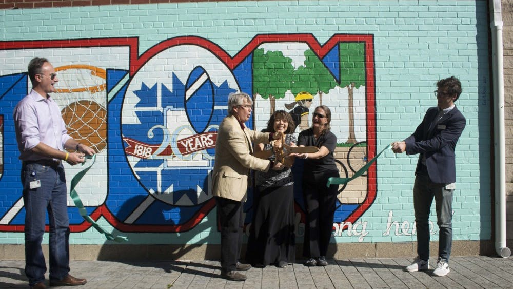 Mayor John Hamilton and mural artist Eva Allen cut the ribbon to officially unveil the mural. The mural in Peoples Park has been in progress since March, but has only recently been finished.