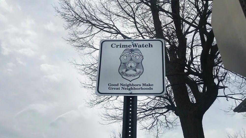 A CrimeWatch sign stands on Tuxedo Street in Indianapolis a few blocks down from where a 21-year-old man was shot Monday. Seven people died from weekend gun violence in Indianapolis.