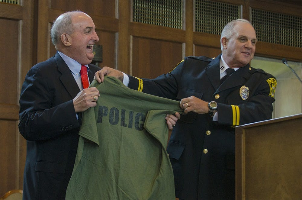 Captain Greg Butler hands IU President Michael McRobbie a police cadet workout shirt after his speech on Aug. 15 at the IU Police Academy graduation ceremony. Thirty-six cadets graduted the academy after a year of training in the academy.