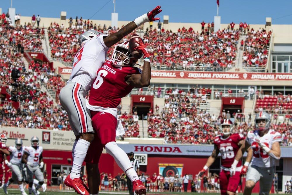 <p>Fans fill the stadium behind fifth-year wide receiver Donavan Hale and an Ohio State defender Sept. 14 in Memorial Stadium. The stadium attendance was 91%, the highest attended home football game in 2019.</p>