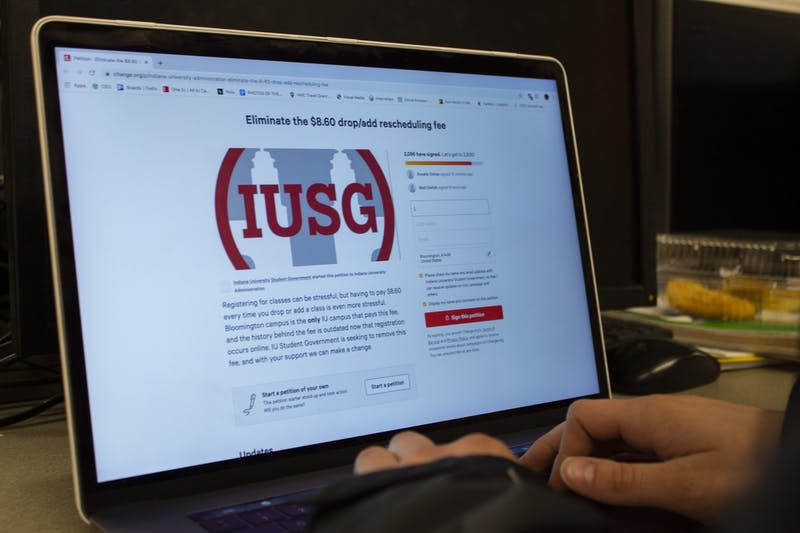 A student looks at a petition to eliminate the drop/add rescheduling fee. Indiana University Student Government started this petition in its efforts to eliminate the fee.