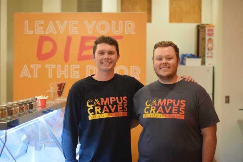 Campus Craves founders Brayden Sammons and Hunter Haines pose behind the counter. The two of them started planning the store their senior year of high school.
