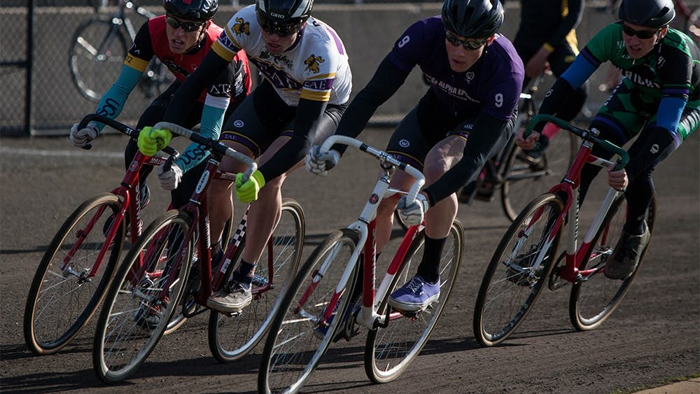 From left to right, Luke Tormoehlen of Delta tau Delta, Andrew and Joe Krahulik of Sigma Alpha Epsilon and Riley Figg of Wright Cycling ride through the first turn at Bill Armstrong Stadium during Miss N Out on Saturday. Joe Krahulik placed first for the men's race, followed closely by his brother Andrew.
