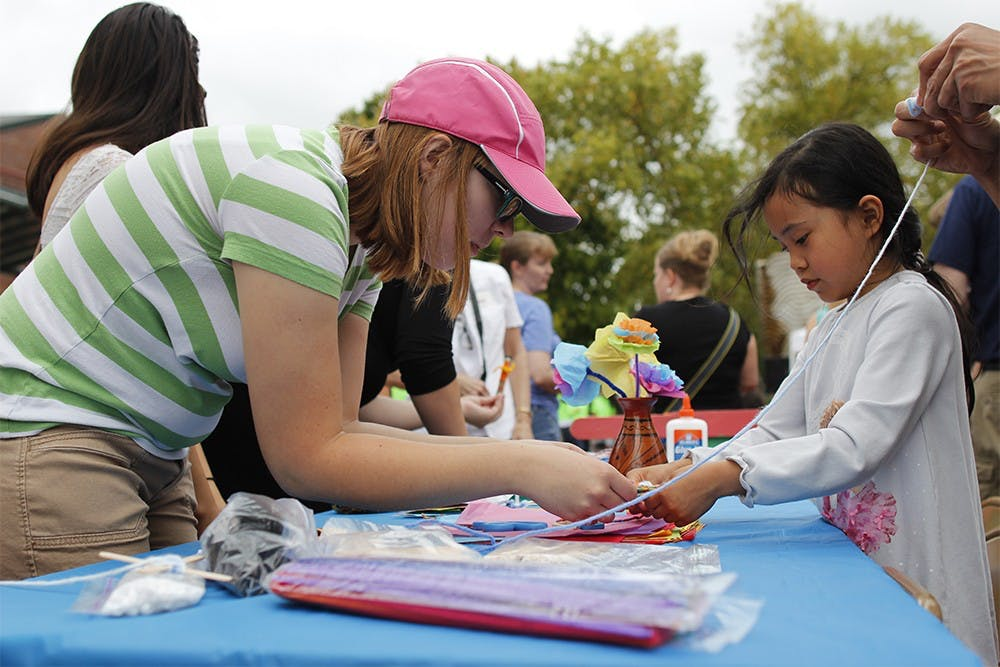 "Mary Bolander, a volunteer with the Bloomington Sister Cities program helps Sasha Luhur, age 6, make a craft with yarn and popscicle sticks during the ""Fiesta del Otoño"" at Showers Plaza during the Farmer's Market Saturday."
