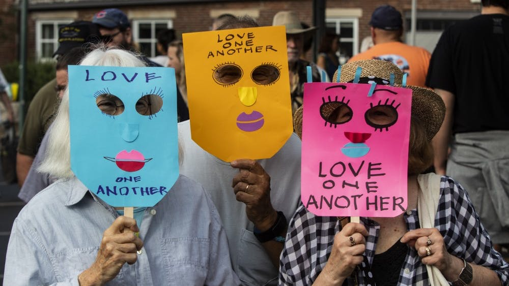 """Demonstrators wear masks that read, """"Love one another,"""" Aug. 17 at the Bloomington Farmers' Market. The demonstrators later stood in front of Schooner Creek Farm's booth with the masks on to protest white supremacy."""
