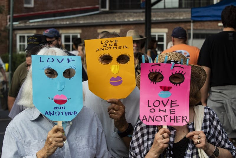 "Demonstrators wear masks that read, ""Love one another,"" Aug. 17 at the Bloomington Farmers' Market. The demonstrators later stood in front of Schooner Creek Farm's booth with the masks on to protest white supremacy."