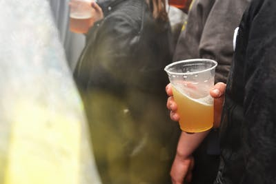 "Someone holds a cup of beer during ""Granfalloon: Outdoor Music Fest"" on May 11 at Upland Brewing Co. The brewing company recently laid off 87% of its employees after Gov. Eric Holcomb announced a ban on dining in at restaurants and bars due to the coronavirus pandemic."