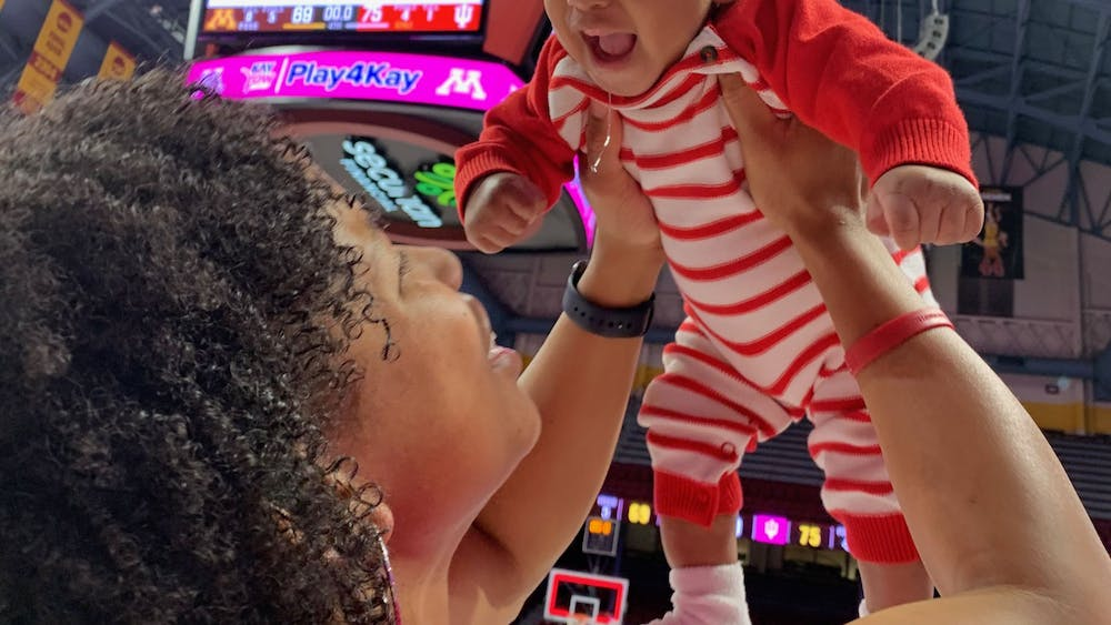 IU assistant coach Janese Constantine holds her son PJ high after a win at Williams Arena in Minneapolis. Janese and PJ made a tradition of posing for a photo with the scoreboard after every road win.