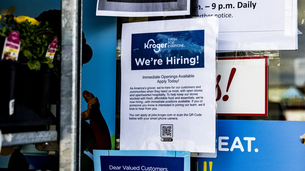 "A ""We're hiring"" sign is displayed on a sliding door April 6 at Kroger. Kroger is hiring more employees in response to the coronavirus pandemic."