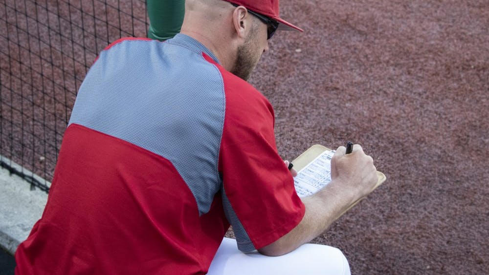 Head coach Jeff Mercer writes on his batting order list May 14 at Bart Kaufman Field. IU played the University of Louisville and lost, 8-7.