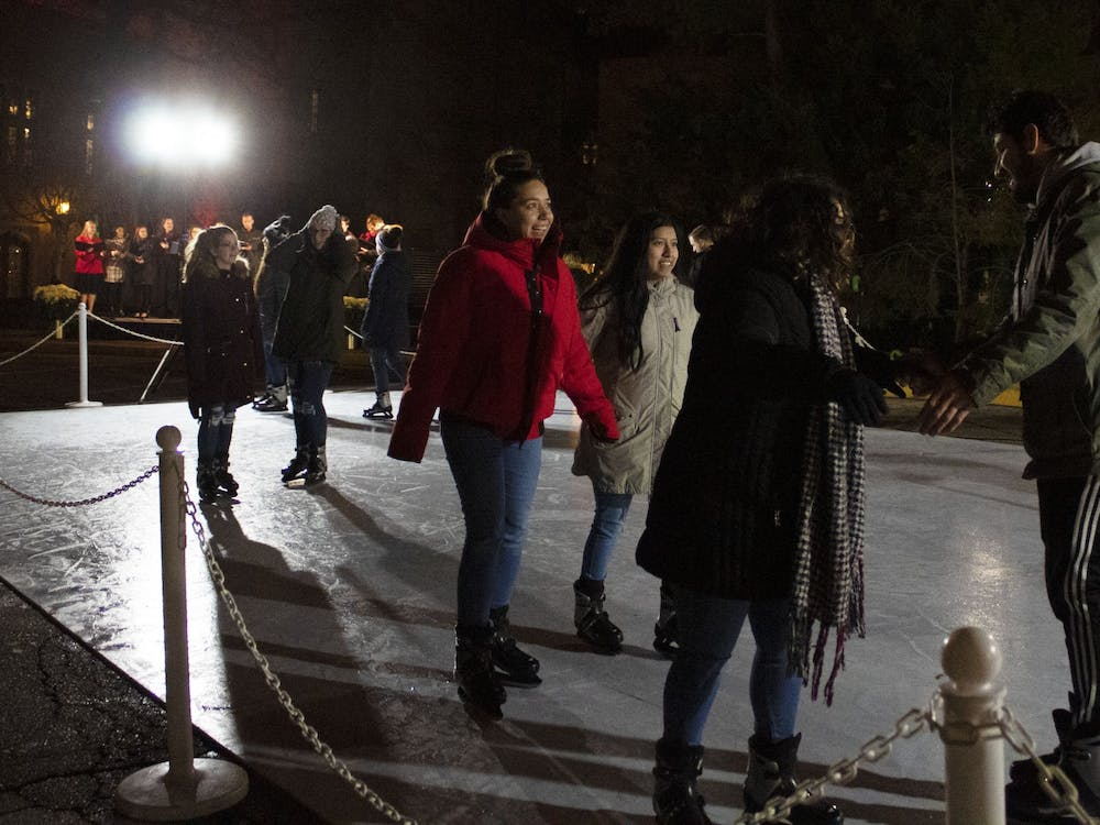 Event attendees skate on an ice rink Dec. 2 in front of the Indiana Memorial Union. The event also included hot chocolate, capella performances and a countdown to light the IMU candle display on the side of the building.