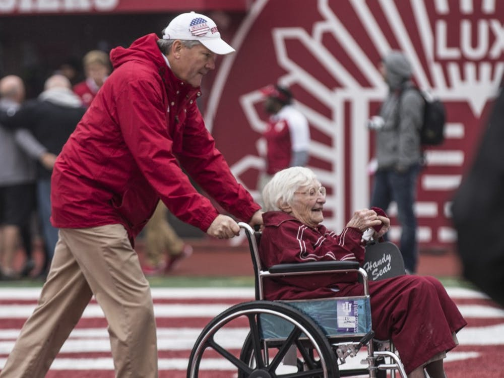 IU Athletics Director Fred Glass wheels the oldest member of 50 Year Varsity Club Donors off the field after an on-field recognition ceremony at the game against Wisconsin on Nov. 4. Glass was appointed athletics director in 2009.
