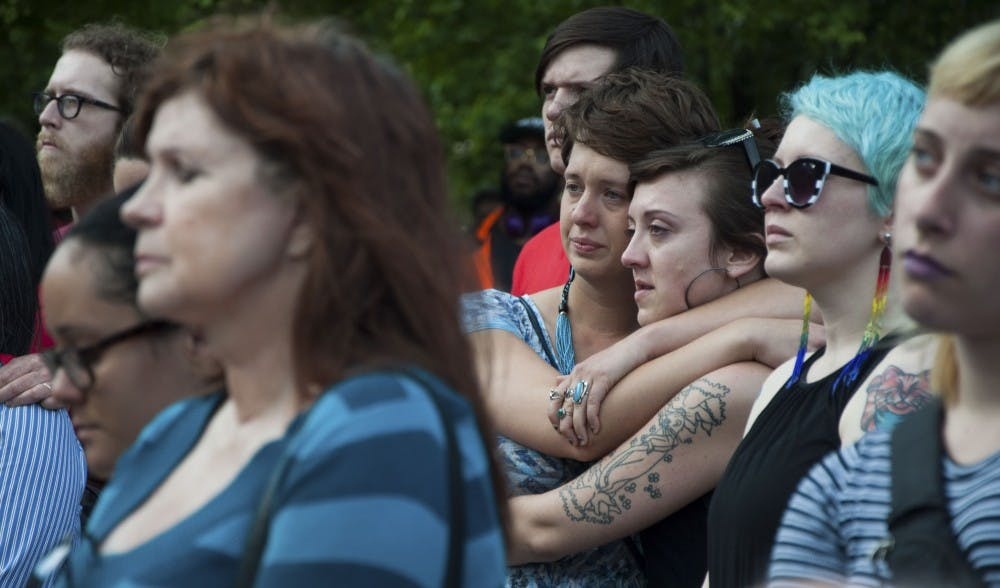 <p>Victoria Brown, left, and Lily Regina comfort each other during the vigil on Tuesday evening at the Bloomington City Hall.</p>