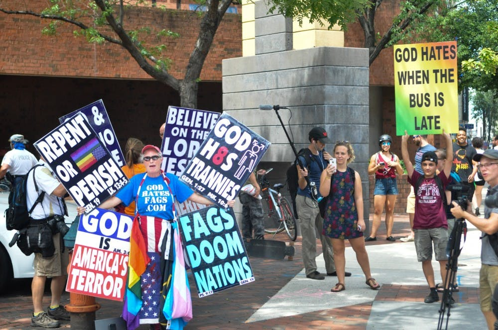 <p>A member of the&nbsp;Westboro Baptist Church sings on the corner outside a Philadelphia LGBT health center on Tuesday afternoon, while police and a single counter protestor stand nearby.</p>