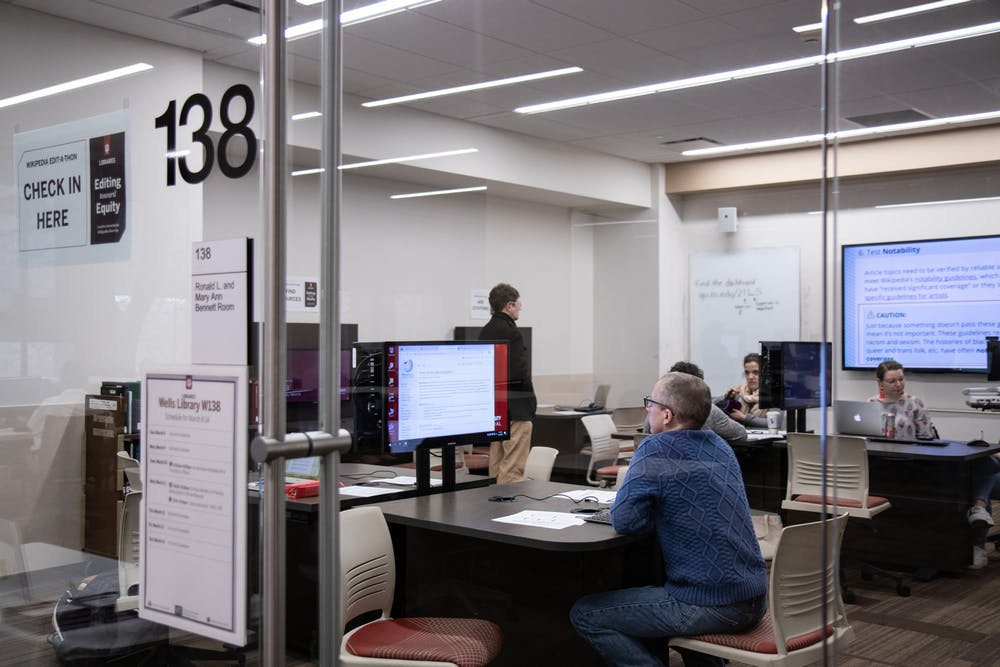 <p>Senior Collections and Reference Associate Edwin Cheek looks for Wikipedia articles March 10 in Wells Library during the Art + Feminism Edit-a-thon. Nine editors added over 1,300 words to Wikipedia articles about arts, feminism and cis and trans women.</p>