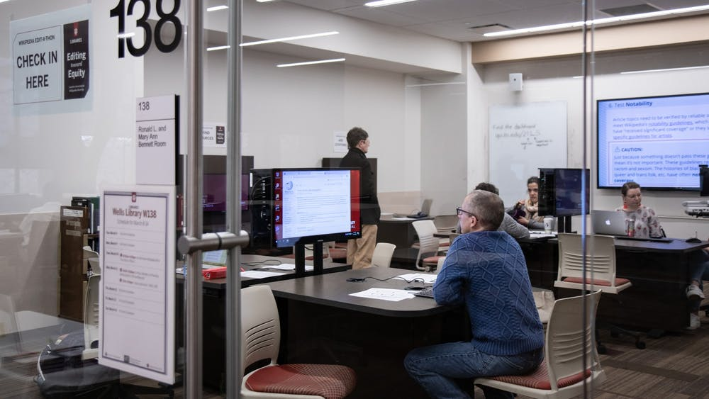 Senior Collections and Reference Associate Edwin Cheek looks for Wikipedia articles March 10 in Wells Library during the Art + Feminism Edit-a-thon. Nine editors added over 1,300 words to Wikipedia articles about arts, feminism and cis and trans women.