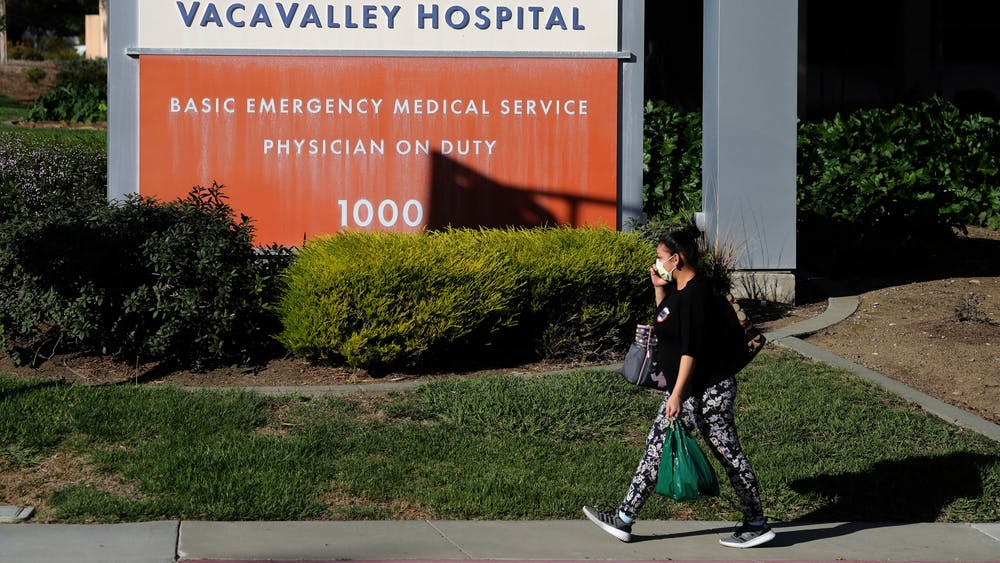 A pedestrian wears a surgical mask as she walks by the VacaValley Hospital on Feb. 27 in Vacaville, California. The Monroe County Health Department released a statement Feb. 28 recommending citizens review their emergency plans to be prepared as the coronavirus continues to spread.