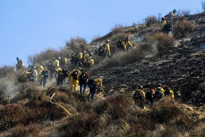 Firefighters clear brush and mop up the hillside along the 14 Freeway, which is closed to traffic through Newhall Pass due to the Saddle Ridge fire Oct. 11 in Newhall, California.