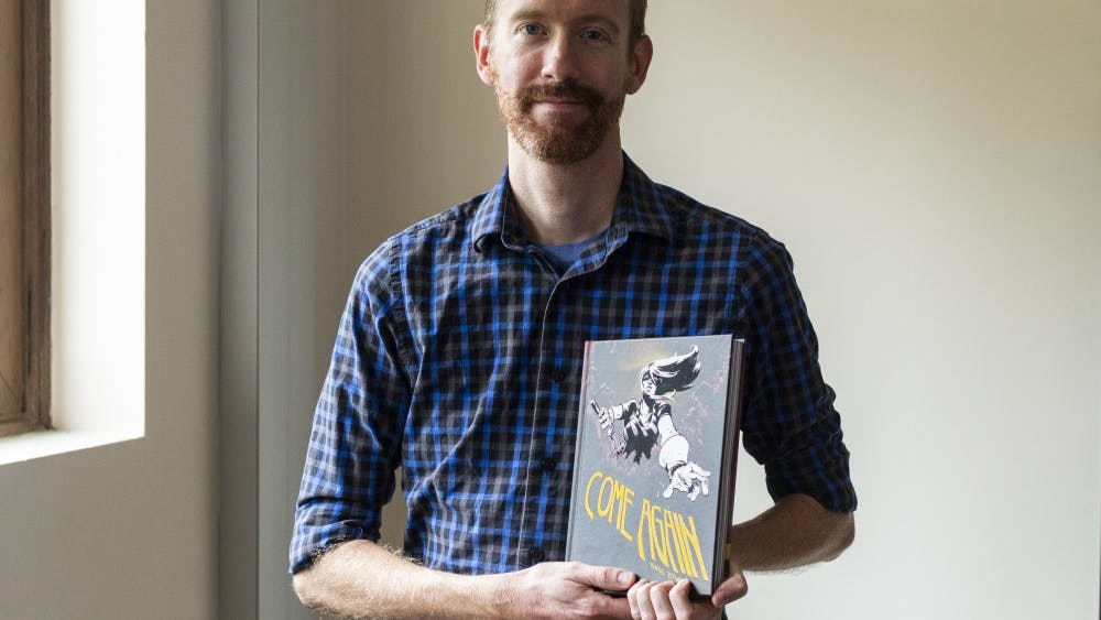 "Graphic novelist and musician Nate Powell holds his new graphic novel ""Come Again,"" which was released July 11."