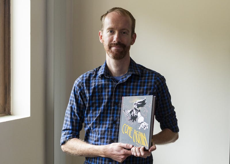 """Graphic novelist and musician Nate Powell holds his new graphic novel """"Come Again,"""" which was released July 11."""
