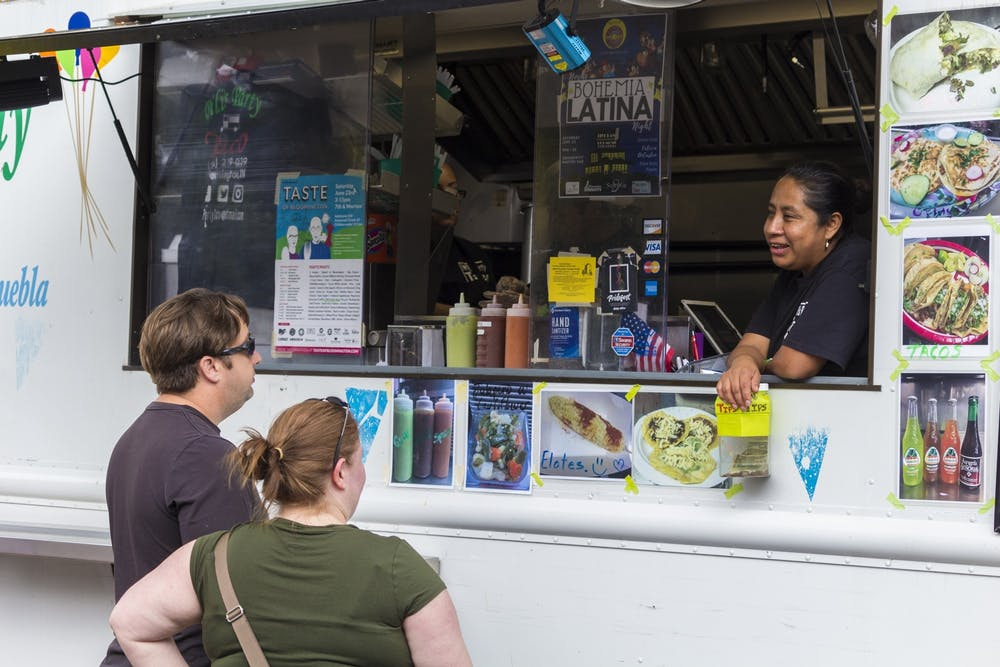 <p>Attendees order food from an employee of Pili's Party Taco truck June 23, 2018, as part of the 36th annual Taste of Bloomington. There are 42 restaurants participating in Taste of Bloomington To-Go from June 19-26.</p>