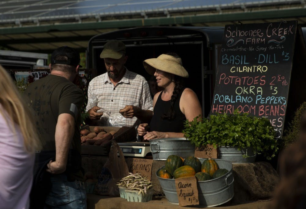 <p>Sarah Dye and her husband Doug Mackey speak to a customer Sept. 28 at their booth for Schooner Creek Farm at the Bloomington Community Farmers' Market. The City of Bloomington alleges that the owners of Schooner Creek Farm broke their contract by filing a federal lawsuit against the city, mayor and other city officials.</p>