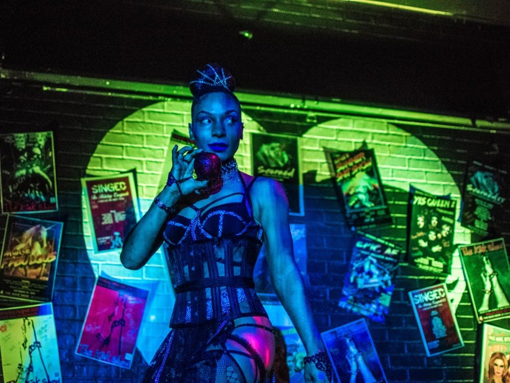 """Burlesque performer Juju Bone holds an apple to her face during her second routine July 20 at the Back Door. """"I do not subscribe to a look,"""" she said. """"I shoot from the hip."""""""