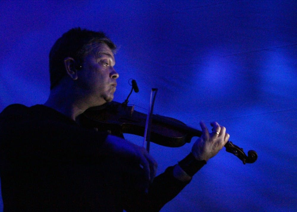 """<p>Robin Cox, musician and faculty with the Department of Music and Arts Technology at IUPUI, plays his violin during the """"Nearing the End of the Hourglass"""" dance performance on Thursday. His wife Stephanie Nugent and her students danced nearby.</p>"""