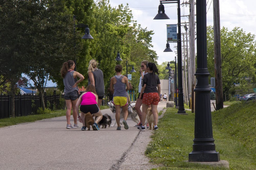 Dog walkers congregate May 28 on the B-Line Trail. IU professors Christina Ludema and Brian Dixon said the safest space to gather with others is outside.