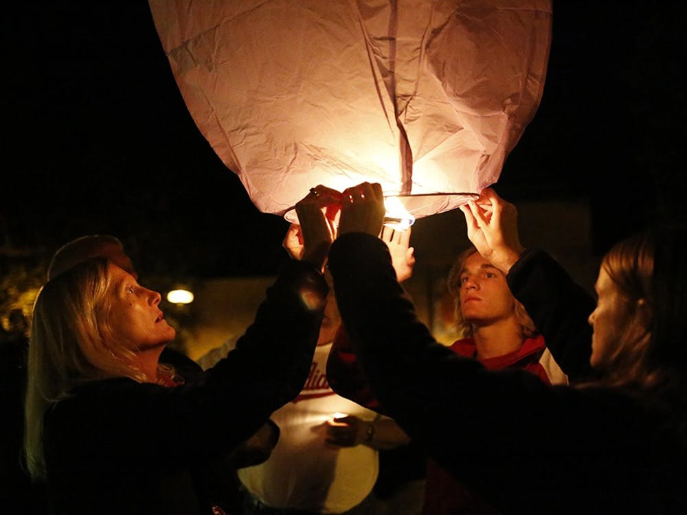 Members of Nicholas Wolfe's family; Jackie Wolfe, left, Mathew Wolfe, middle, Samantha Wolfe, right, hold up the final paper latern to be released Sunday at Showalter Fountain during a vigil for Nicholas Wolfe, an IU student who recently died.