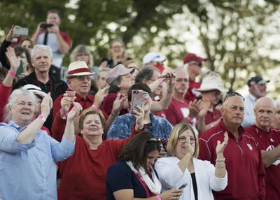 Parade spectators cheer as the Marching Hundred perform at the intersection of 17th Street and Woodlawn Avenue on Friday evening as part of the homecoming parade. The parade started at the Indiana Memorial Union and worked its way north to the tailgating fields.