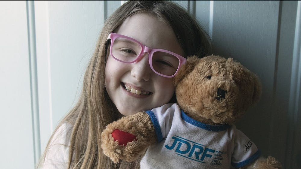 Eight-year-old Lucy poses for a picture with her JDRF bear. Rufus, the bear, is given to patients to practice injecting into.