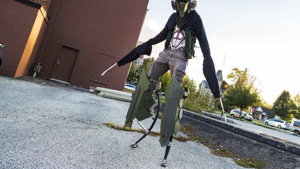 "Reilly Donaldson stands after putting on his ""Skeleton Harvester"" costume Oct. 20 in the parking lot of Framemakers where he works. Donaldson uses the parking lot to get into his costume before heading toward downtown Bloomington."