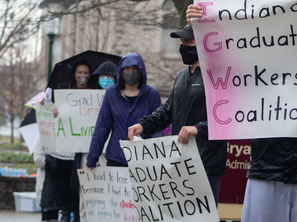 Graduate workers stand along the road March 11 in front of Bryan Hall with picket signs in protest of fees. IU accused the Indiana Graduate Workers Coalition of a trademark violation in an email Wednesday.