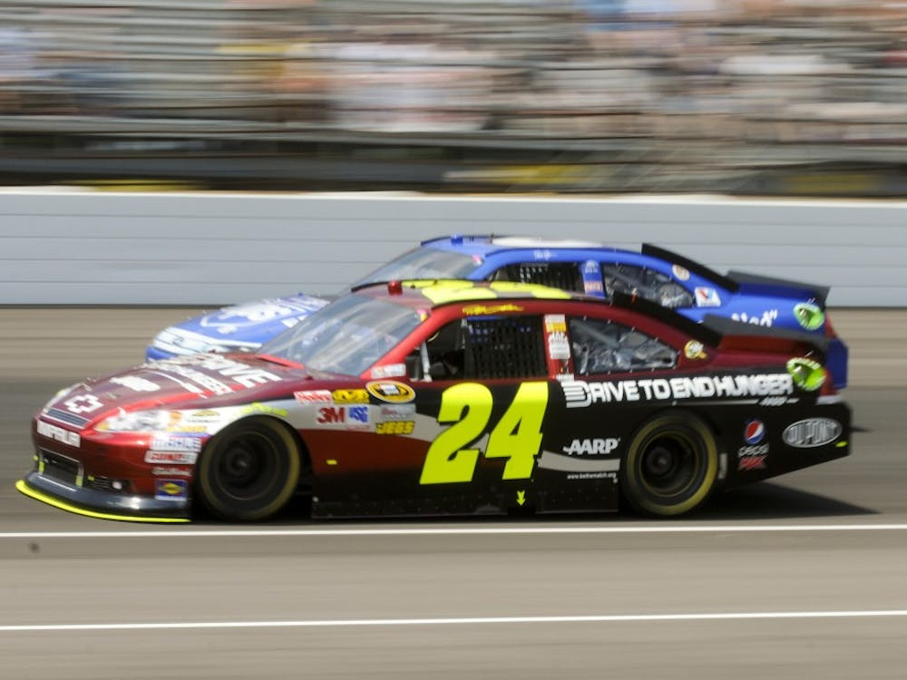 Jeff Gordon drives his Drive To End Hunger Chevrolet past pole sitter David Ragan in turn four near the start of the Brickyard 400 on July 31, 2014 at the Indianapolis Motor Speedway.