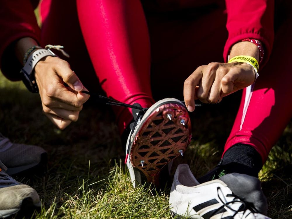 An IU cross country athlete ties their shoes in October 2019. The Hoosiers competed at the 2021 NCAA Cross Country Championships on March 15, with the men's team finishing in 26th place and the women finishing in 19th.
