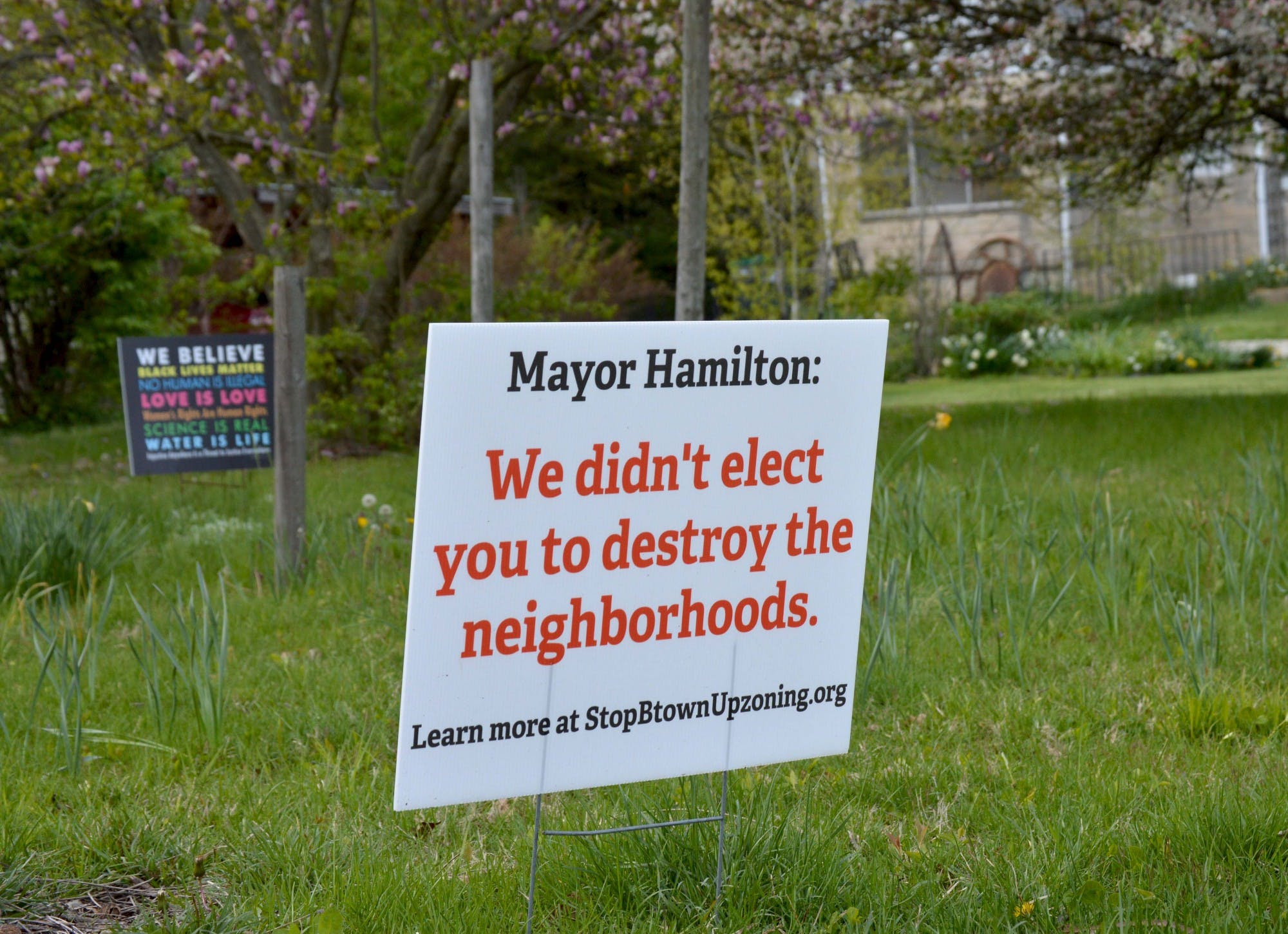 A sign near Bryan Park reads 'Mayor Hamilton: We didn't elect you to destroy the neighborhoods.' A proposed zoning district would allow duplexes and similar structures to be built in traditionally single-family home neighborhoods.
