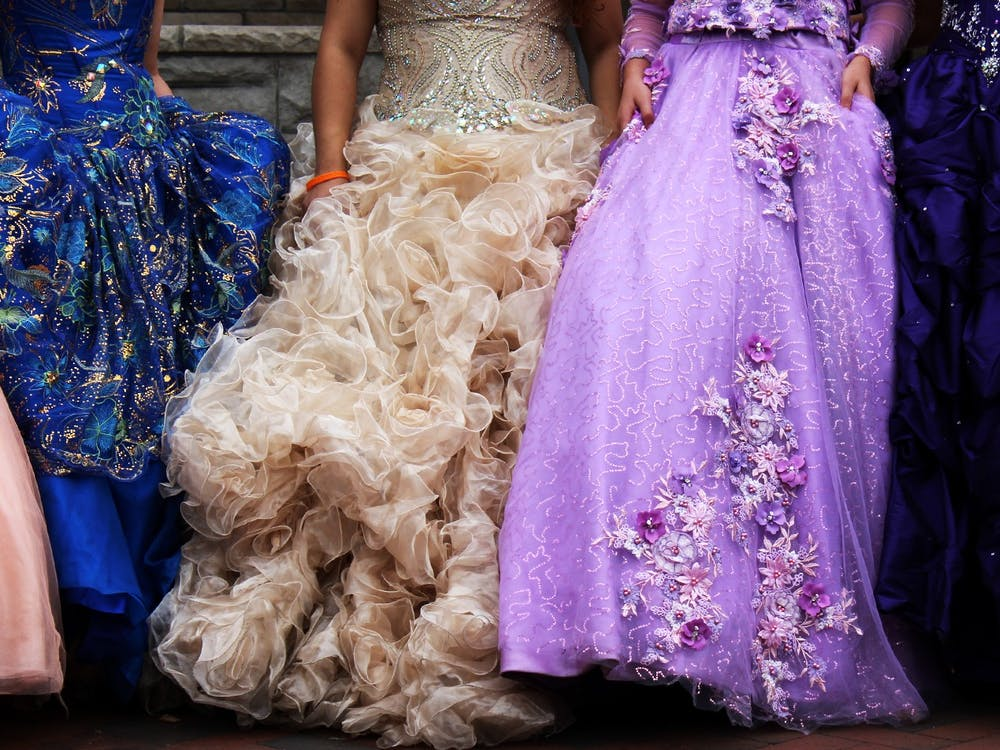 Dress models pose as family members and friends photograph them Sept. 26 on East Kirkwood Avenue. Quinceañera dresses cost between $300 and $900 at retailers such as Disney, according to the New York Times.