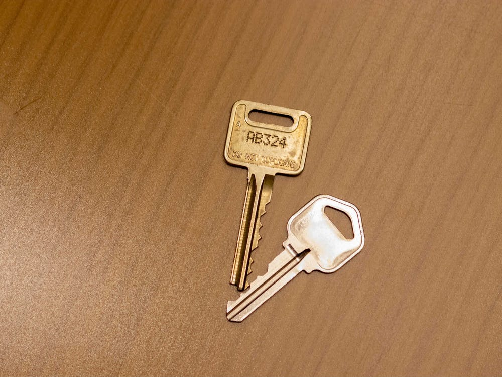 Two keys sit on a table.