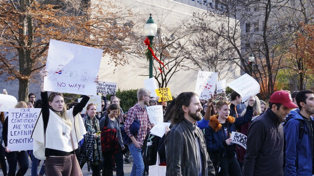 More than 100 grad students from all areas of study march from Woodburn Hall to Bryan Hall to deliver a petition to President Michael McRobbie to publicly oppose a House of Representatives bill taxing graduate students' tuition waivers. The GOP-backed bill would repeal tax exemptions for students receiving tuition waivers and would affect more than 2,100 IU students.